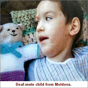Photograph: Deaf-mute child from Moldova with her knitted teddy.