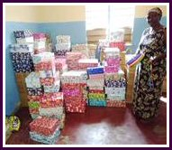 Photograph: Woman posing with shoe boxes and gifts donated by Lutterworth Rotary.